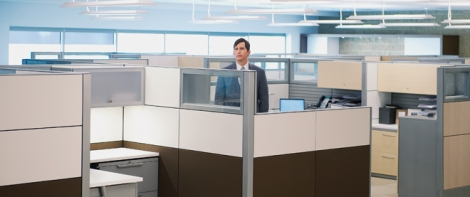 Lonely businessman standing in a cubicle
